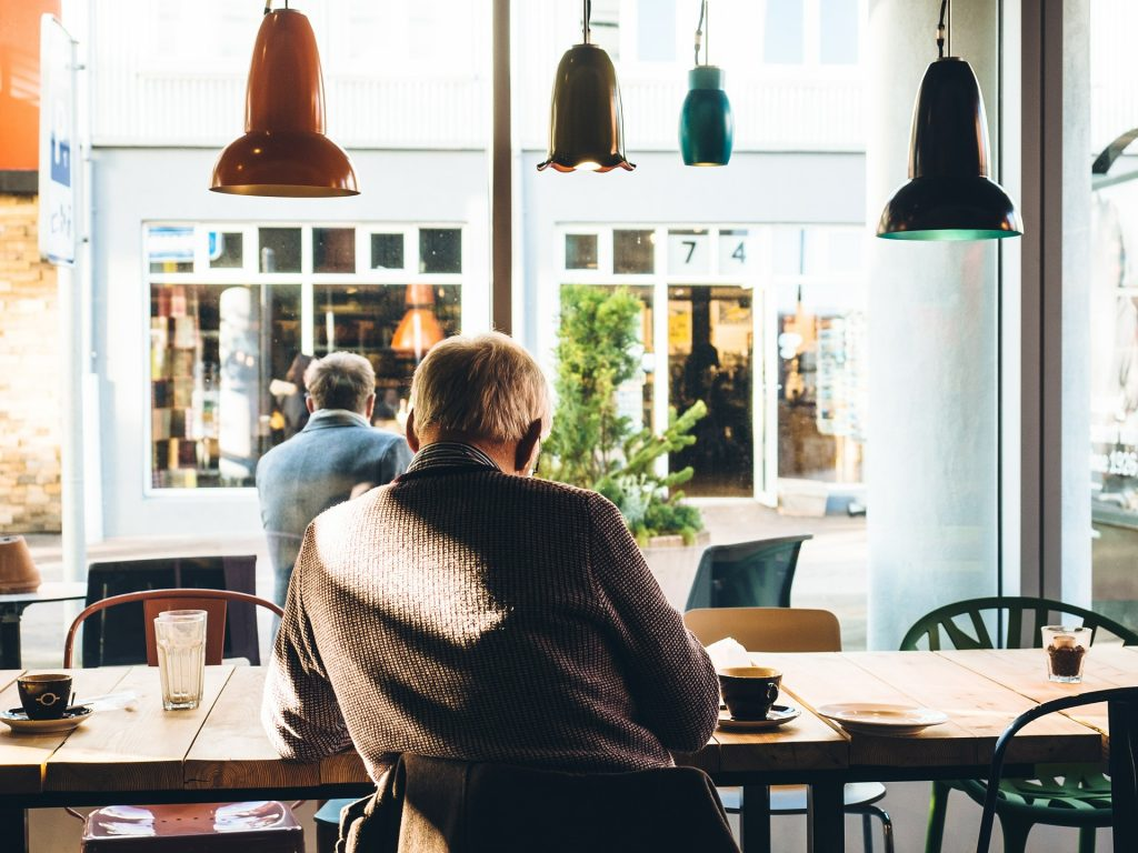 Elderly man eating at table